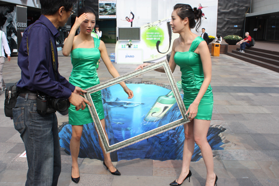 One optical illusion upon another - Jinfro ladies holding a panting frame over 3D art