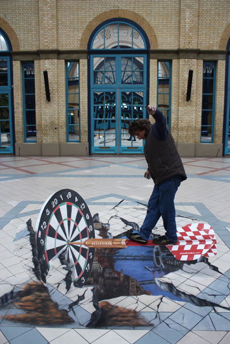 Man interacting with 3D street painting illusion for Ladbrokes, London