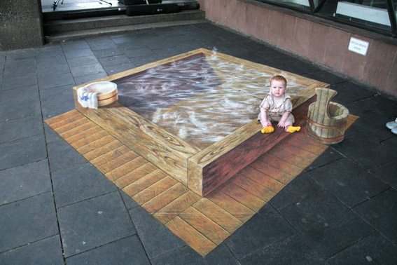 Baby posing with 3D optical illusion street painting for Fuji TV