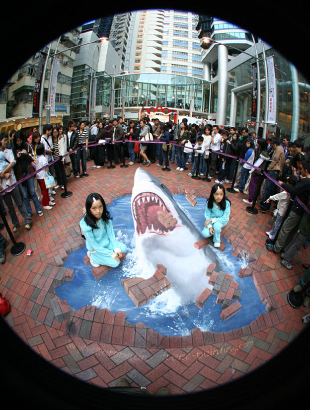 Twins posing with 3D optical illusion in Hong Kong
