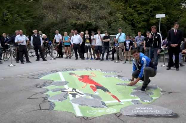 Mario Gomez posing with 3D pavement drawing from Puma