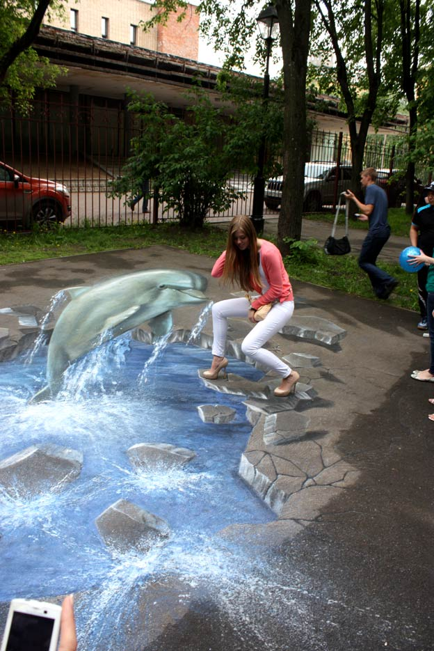 Girl interacting with 3D pavement painting at 3D Pictures on Asphalt Festival, Moscow