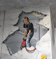 Anamorphic mural of a guy drilling into an elevator