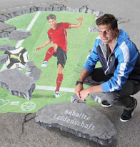 Mario Gomez poses with a 3D street painting of a football player